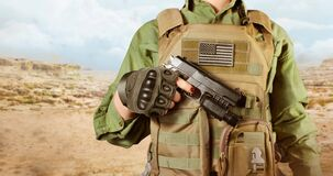 American military soldier woman`s hand holding a gun