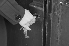 Hand use the key for unlocking door. Monochrome photo Royalty Free Stock Photography