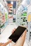 Hand use smart phone on blurred photo of supermarket shelf Royalty Free Stock Photo