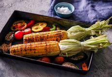 Hand uses chopsticks to pickup tasty noodles with smokes.Homemade organic grilled summer vegetables on rustic table. Corn, pepper,. Homemade organic grilled Royalty Free Stock Images