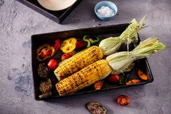 Hand uses chopsticks to pickup tasty noodles with smokes.Homemade organic grilled summer vegetables on rustic table. Corn, pepper,. Homemade organic grilled Royalty Free Stock Photo