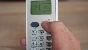 Using the air conditioner remote close up stock footage