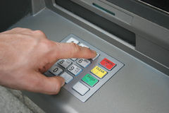 Hand using ATM keyboard. Males hand using automatic teller keypad to enter pin number Royalty Free Stock Photo