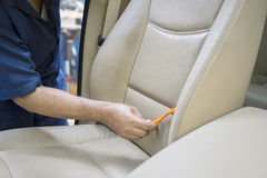 Hand using a brush to clean car seat Stock Photos