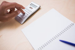 Hand using calculator at desk Stock Photo