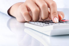Hand using calculator on white Royalty Free Stock Images