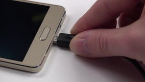Hand using charging of mobile phone on white, close up stock video footage
