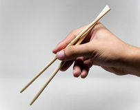 Hand using chopsticks Stock Images