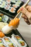 Hand using chopsticks pick Sushi, Sashimi and Futomaki rolls.  Fresh made Sushi set with salmon, prawns, wasabi and ginger. Tradit Stock Images