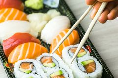 Hand using chopsticks pick Sushi, Sashimi and Futomaki rolls.  Fresh made Sushi set with salmon, prawns, wasabi and ginger. Tradit Royalty Free Stock Photos