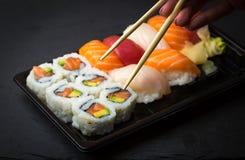 Hand using chopsticks pick Sushi and Sashimi rolls on a black stone slatter. Fresh made Sushi set with salmon, prawns, wasabi and Stock Image