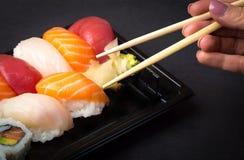 Hand using chopsticks pick.Sushi and Sashimi rolls on a black stone slatter. Fresh made Sushi set with salmon, prawns, wasabi an Royalty Free Stock Photography