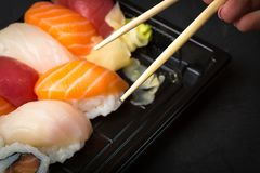 Hand using chopsticks pick. Sushi and Sashimi rolls on a black stone slatter. Fresh made Sushi set with salmon, prawns, wasabi and Royalty Free Stock Image