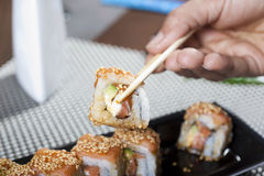 Hand using chopsticks with sushi Stock Image