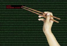 Hand using chopsticks to pinch the last password on binary compu Stock Photography