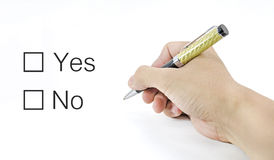 Hand using a classic pen decide to choice yes or no. A Hand using a classic pen decide to choice yes or no royalty free stock image