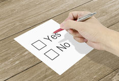 Hand using a classic pen decide to choice yes or no. A Hand using a classic pen decide to choice yes or no royalty free stock photo