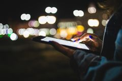 Woman hand using digital tablet on night beauty light bokeh in city stock image