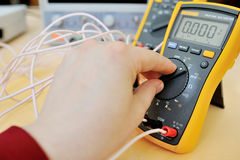 Hand using electronic multimeter stock photo