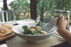 A hand using fork to scoop up Ceasar salad to eat with pizza on dining table. In the restaurant Stock Photo