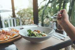 A hand using fork to scoop up Ceasar salad to eat with pizza on dining table. In the restaurant Royalty Free Stock Photography