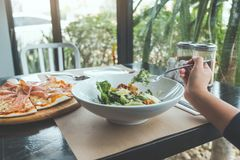 A hand using fork to scoop up Ceasar salad to eat with pizza on dining table. In the restaurant Royalty Free Stock Photo