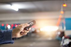 Hand using key remote control of car in underground royalty free stock image