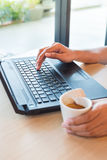 Hand using a keyboard of back notebook on the wooden table and hand holding aromatic cappuccino, white coffee cup Stock Photo