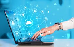 Hand using laptop with centralized linked cloud system concept. Hand using laptop with centralized cloud computing system and network security conceptn royalty free stock photo