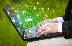 Hand using laptop with centralized linked cloud system concept. Hand using laptop with centralized cloud computing system and network security concept royalty free stock image