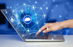 Hand using laptop with centralized linked cloud system concept. Hand using laptop with centralized cloud computing system and network security concept royalty free stock photo