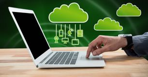 Hand using laptop with clouds icon and hanging connection devices and green background. Digital composite of Hand using laptop with clouds icon and hanging Royalty Free Stock Photos