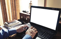 Hand using laptop on messy working table, with white copysapce. vintage tone Stock Photo