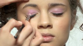 Hand using makeup brush, eyeshadow. Face of a model stock footage