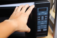 Hand using microwave oven Stock Image