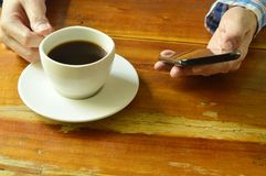 Hand using mobile phone while drinking black coffee. Cup Royalty Free Stock Photo