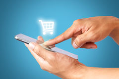 Hand using mobile phone online shopping, business and ecommerce concept. Hand using mobile phone with cart icon and blue background, online shopping, business Stock Photos