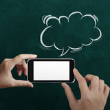 Hand using mobile phone with speech bubble. On chalkboard Royalty Free Stock Image