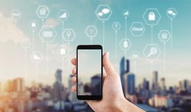 Hand using mobile smart phone with application icons. Such as online message, internet payment, banking, online shopping and etc. city sunrise background Royalty Free Stock Image