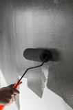 Hand using paint roller  applying grey paint on white wall. Royalty Free Stock Photography