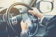 Hand using phone sending a text while driving to work Royalty Free Stock Photo