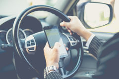 Hand using phone sending a text while driving to work Royalty Free Stock Photos
