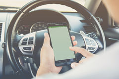 Hand using phone sending a text while driving to work Stock Photography