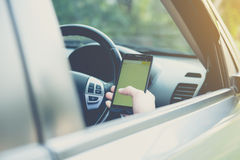 Hand using phone sending a text while driving to work Royalty Free Stock Image