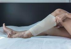 Hand using put on elastic bandage with legs having knee or leg pain. Hand using put on elastic bandage with leg having knee or legs pain stock photo