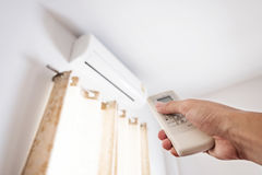 Hand using remote control air conditioning, representing energy saving concepts Stock Photography