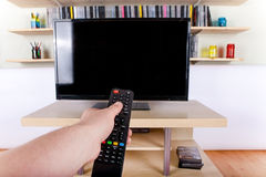 Hand using remote control in front of the TV. A Hand using remote control in front of the TV Royalty Free Stock Photos