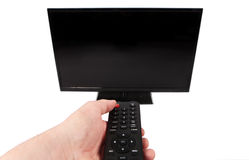 Hand using remote control in front of the TV with empty black sc Royalty Free Stock Photography