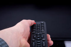 Hand using a remote control in front of the TV screen. A Hand using a remote control in front of the TV screen Stock Photos