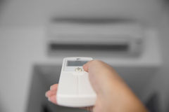 A hand using a remote to activating air conditioning machine Stock Image